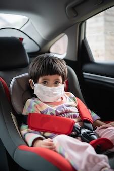 Bébé mignon assis dans un siège de sécurité de voiture