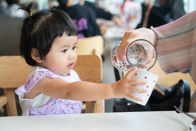 Bébé mignon boit de l'eau au restaurant