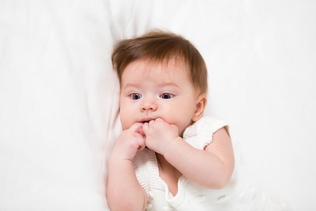 Le bébé mignon a une dentition, elle ronge les doigts parce que la première dent