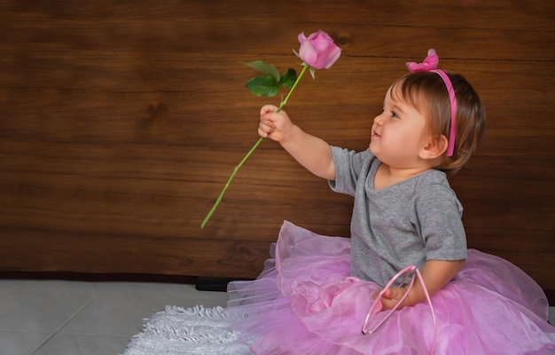 Bébé mignon avec fleur. enfant sur le sol dans une robe rose, une fille regarde une rose rose