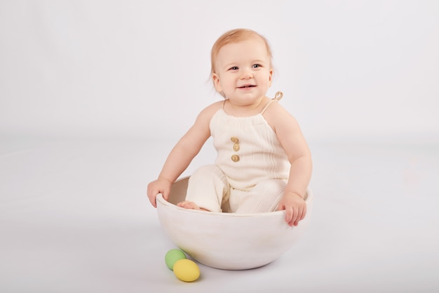 Bébé mignon avec des oeufs de pâques peints