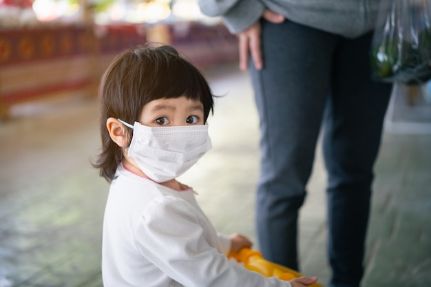 Bébé mignon portant un masque chirurgical, covid-19 coronavirus protection concept