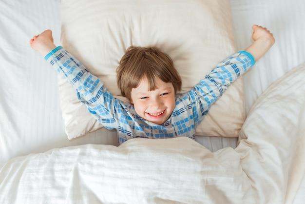 Le bébé mignon s'est réveillé, s'étire le matin dans son lit