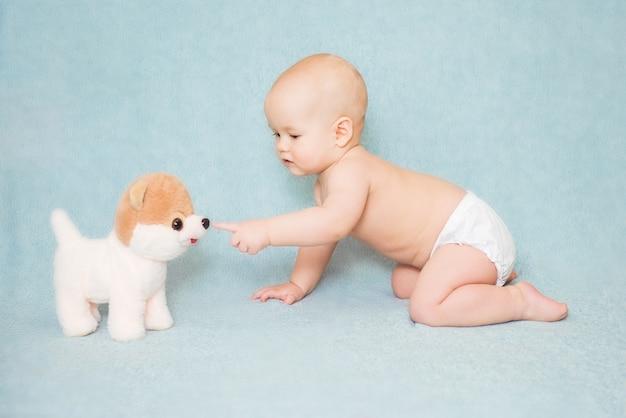 Bébé mignon touche le nez d'un chien jouet