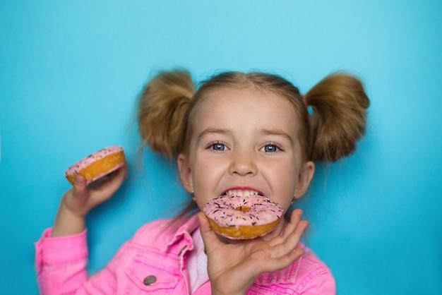 Le bébé mord un beignet sucré aime les bonbons mais il est nocif pour les dents