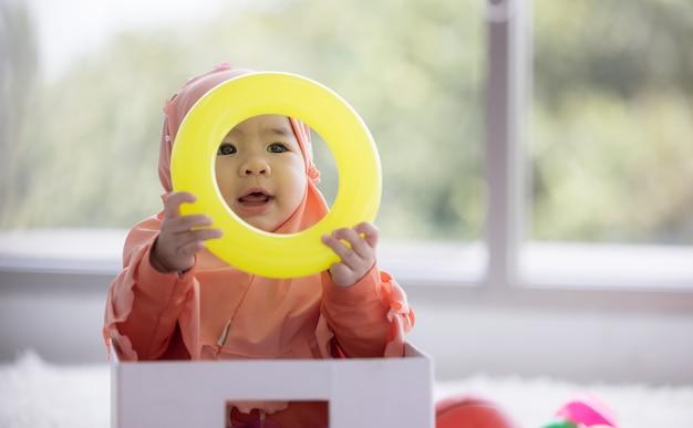 Bébé musulman joue avec des jouets colorés dans le salon