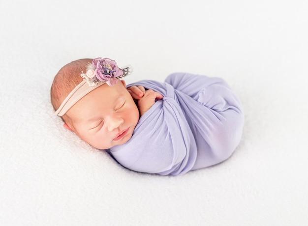 Bébé nouveau-né dans une bande fleurie et une couverture, attaché avec une tresse