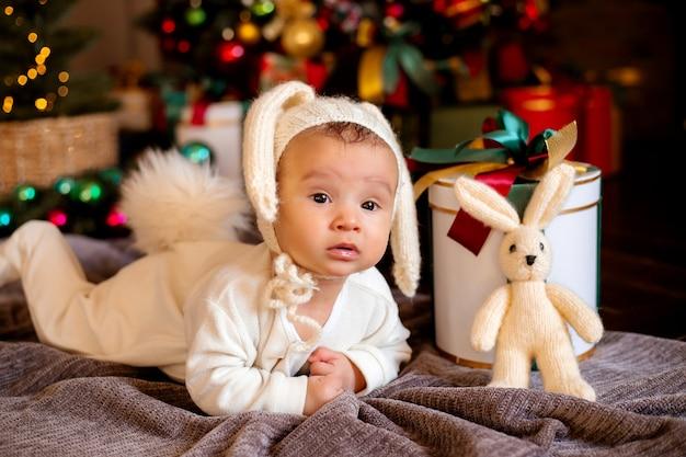Bébé nouveau-né dans un costume de lapin se trouve sur la couverture grise près de l'arbre de noël festif
