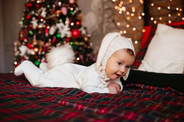 Bébé nouveau-né dans un costume de lapin se trouve sur la couverture rouge près de l'arbre de noël festif
