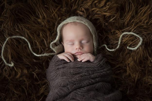 Bébé nouveau-né dort dans un gros plan de fourrure sombre