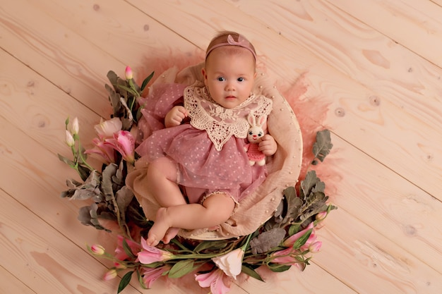 Bébé nouveau-né fille dormant dans un panier rétro avec des fleurs de jardin rose
