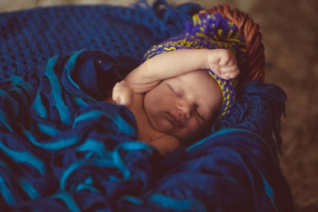 Le bébé nouveau-né incroyable et doux dort dans le panier