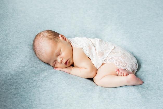 Bébé nouveau-né mignon sur fond bleu