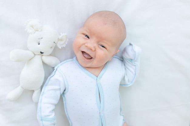 Bébé nouveau-né souriant ou riant allongé à l'arrière du berceau sur le lit en coton à la maison avant d'aller au lit avec une peluche, semaine de bébé, le concept de naissance et de petite enfance, vue de dessus.