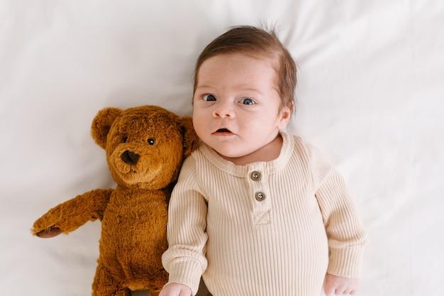 Bébé avec un ours en peluche sur la vue de dessus de lit