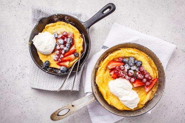 Bébé pancake néerlandais avec baies et crème dans une poêle en fonte, vue de dessus.