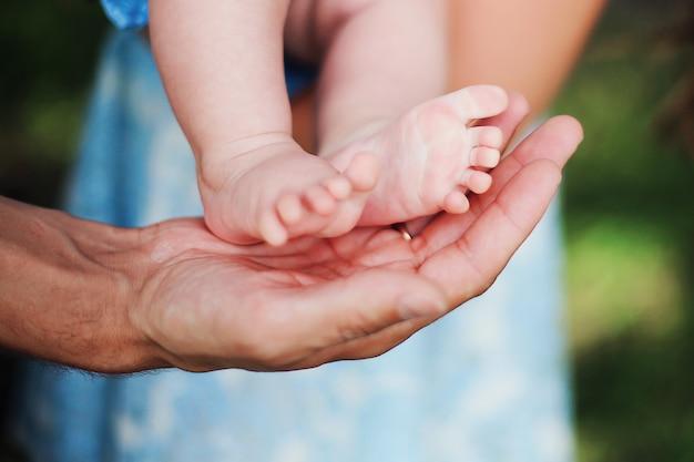 Bébé petit pieds dans les mains des parents. jour d'été.