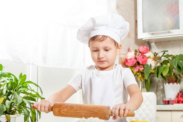 Bébé pétrir la pâte dans la farine