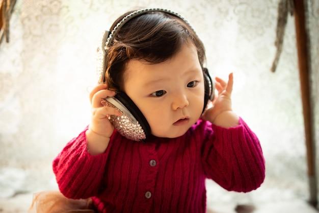 Un bébé portant un casque et écoutant de la musique
