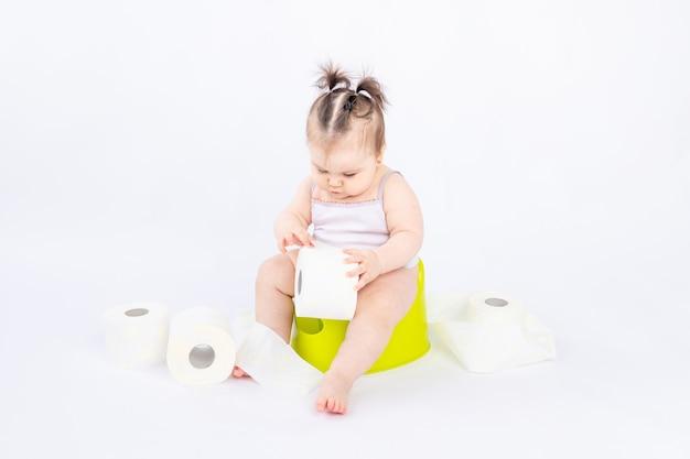 Bébé sur un pot vert avec du papier toilette sur blanc