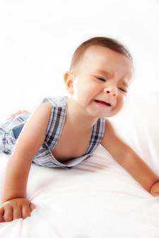 Bébé qui pleure sur un fond blanc.