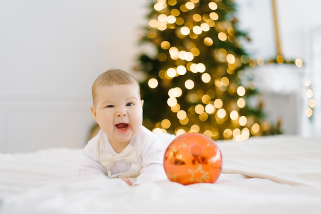 Le bébé rit, couvrant un œil, allongé sur le lit dans le contexte des lumières de noël