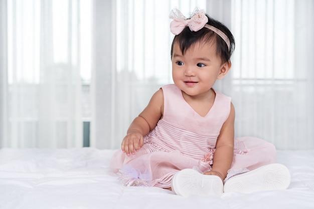 Bébé en robe rose sur le lit