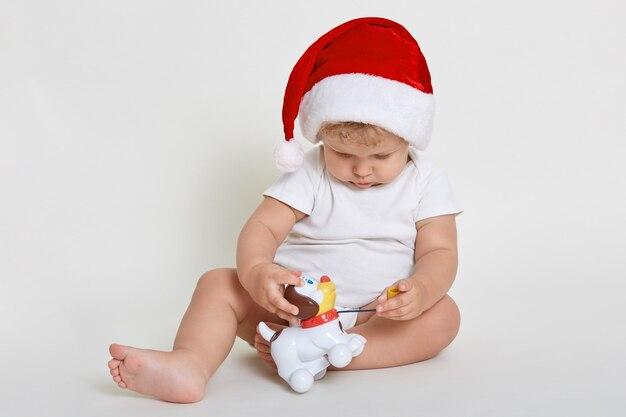 Bébé robes chapeau de père noël posant isolé sur un mur blanc tout en étant assis pieds nus sur le sol et jouant avec un chien en plastique, enfant regardant jouet avec intérêt.