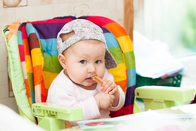 Le bébé s'assied dans la chaise haute et mange.