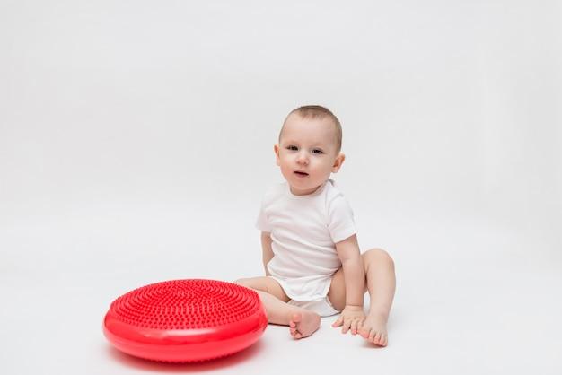Le bébé s'assoit et joue avec le coussin d'équilibrage. équilibreur rouge. orthopédiste