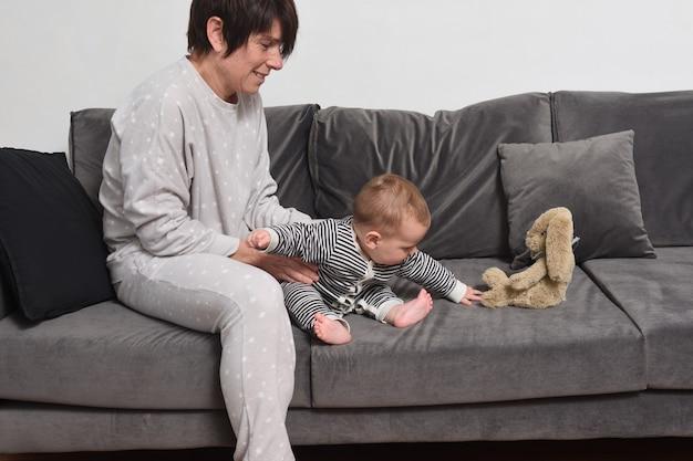 Bébé avec sa mère assise sur le canapé le bébé veut prendre la poupée