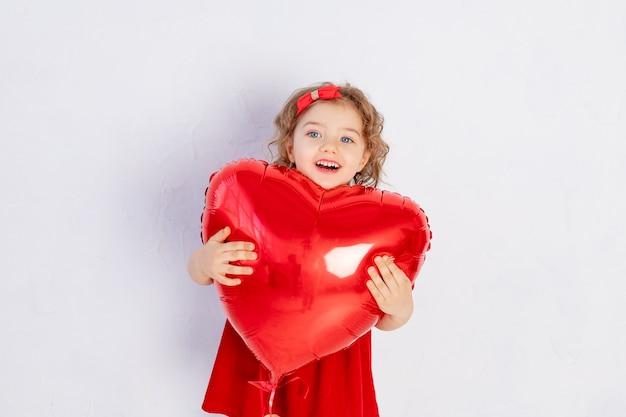 Bébé de la saint-valentin. une petite fille en robe rouge tient une grosse boule en forme de coeur