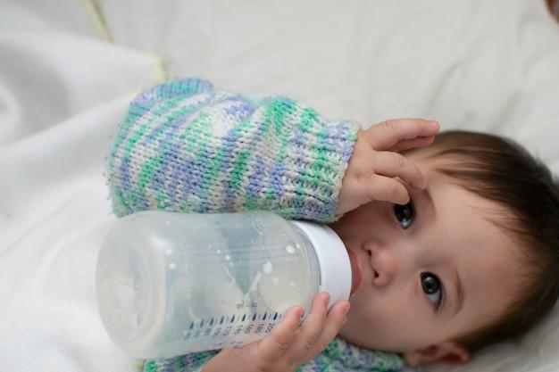 Bébé se nourrit pour la première fois en tenant la bouteille de lait, se couche sur le lit