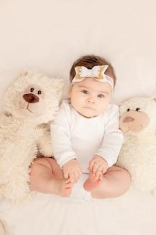 Le bébé a six mois dans un berceau dans un body blanc avec un ours en peluche