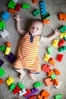 Bébé sur le sol entouré de blocs de jouets colorés