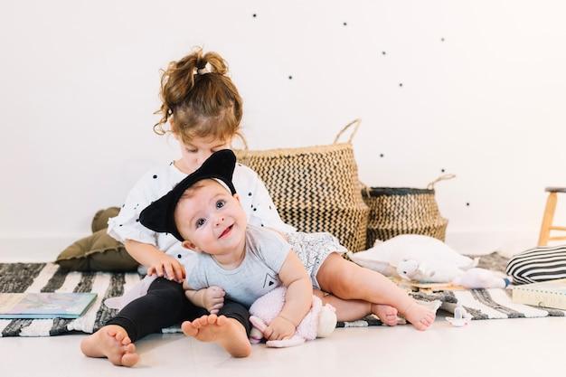 Bébé souriant sur les jambes de la fille