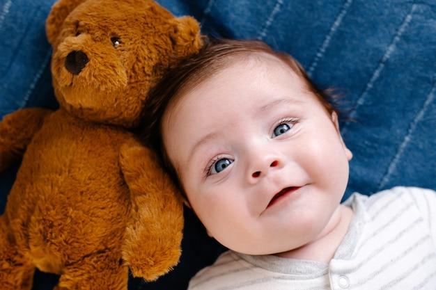 Bébé souriant avec jouet sur fond bleu vue de dessus