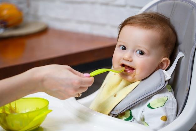 Un bébé souriant de neuf mois est assis à une table blanche dans une chaise haute et mange avec une cuillère dans un bol. maman nourrit le bébé à la cuillère. arrière-plan flou. alimentation saine pour les enfants. nourriture pour enfants.
