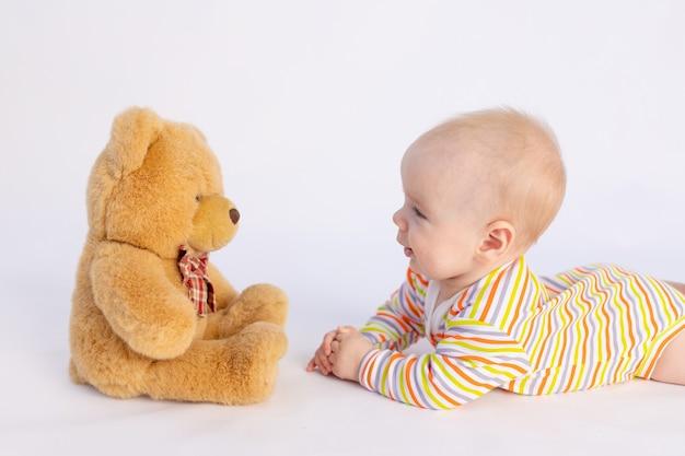 Bébé souriant de six mois se trouve isolé avec un ours en peluche doux