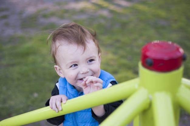 Bébé sourit dans l'aire de jeux d'un parc
