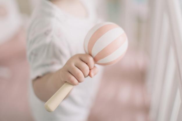 Bébé tenant dans les mains pouf en bois