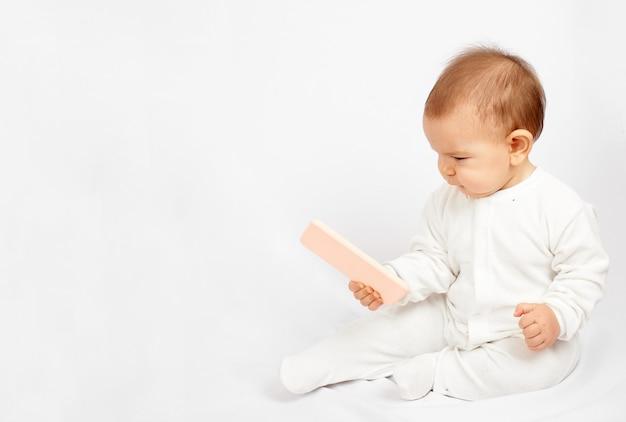 Bébé tenant un téléphone portable isolé sur fond blanc génération z