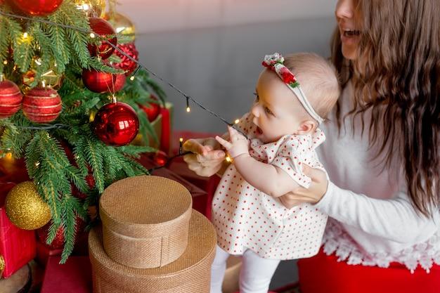 Un bébé tire une guirlande avec des lumières d'un arbre de noël