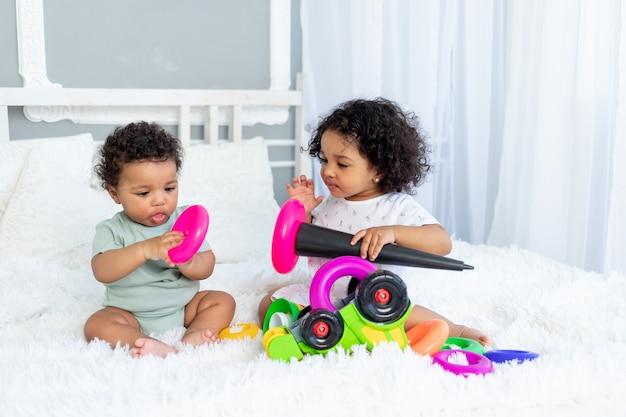 Les bébés afro-américains jouent et collectionnent une pyramide colorée à la maison sur le lit