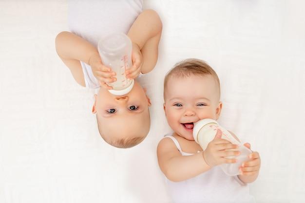Bébés jumeaux garçon et fille avec une bouteille de lait sur un lit blanc à la maison, concept de nourriture pour bébé