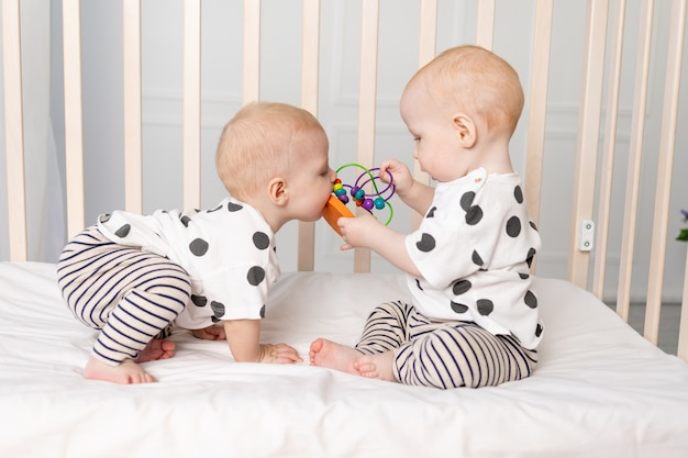Les bébés jumeaux jouent dans le berceau, développement précoce des enfants jusqu'à un an