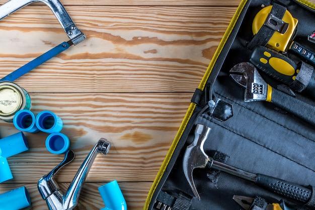 Bec en pvc, coude en pvc, raccordant le tuyau et le ruban adhésif sur fond en bois.