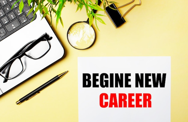 Begine new career est écrit en rouge sur un morceau de papier blanc sur une table jaune clair à côté d'un ordinateur portable, d'un stylo, d'une loupe, de lunettes et d'une plante verte.