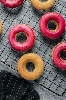 Beignes fraîchement cuits au four avec glaçage rose vif sur la grille de refroidissement