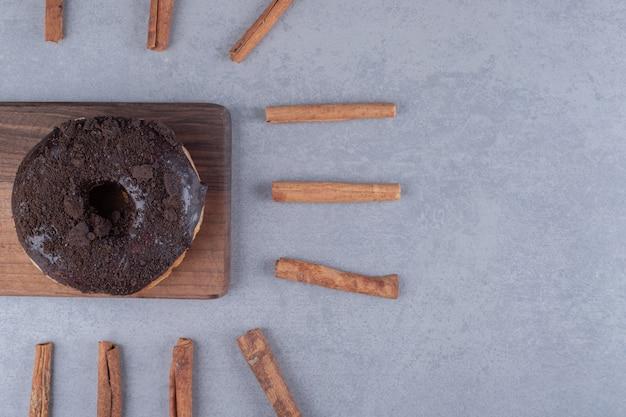Un beignet et des bâtons de cannelle sur une surface en marbre